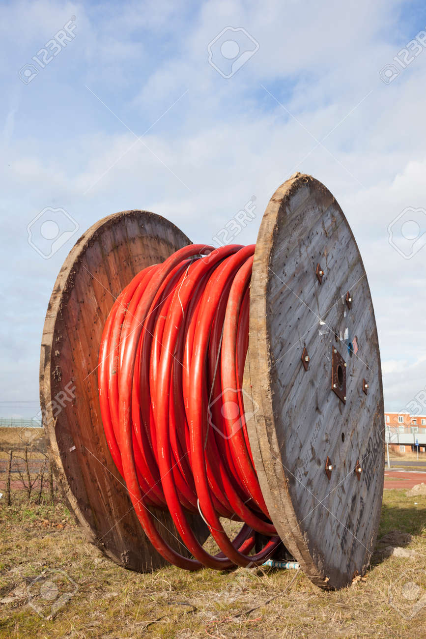 Large Wooden Spool With Heavy Red Underground Cable Stock Photo