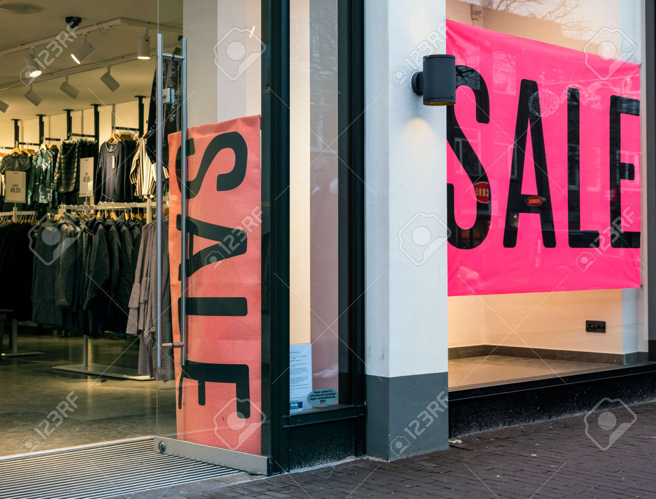 c4b693d0f4a Stock Photo - the word sale in shop window of clothing store with open door