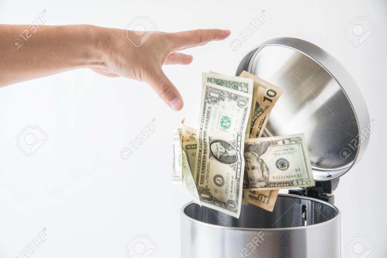 throwing away dollar in trashcan - 65456778