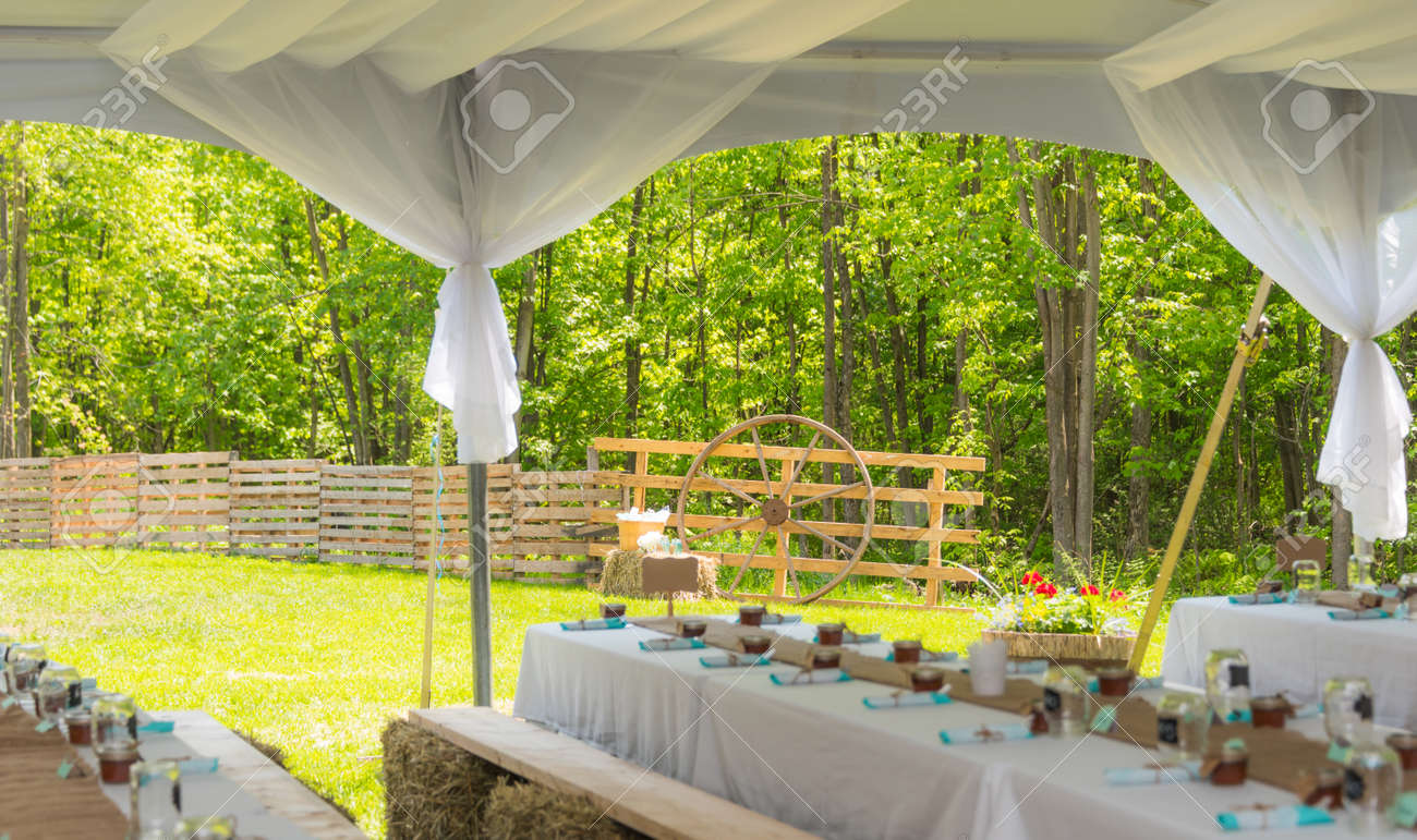 Stock Photo   Sunny Outdoor Country Wedding Reception Dinner Party Tables  Ready To Receive Guests. Seating On Planks Atop Small Hay Bails At Tables.