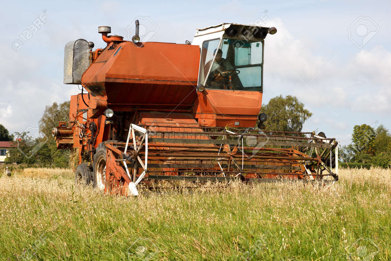 old grain harvester working on field Stock Photo - 14981349