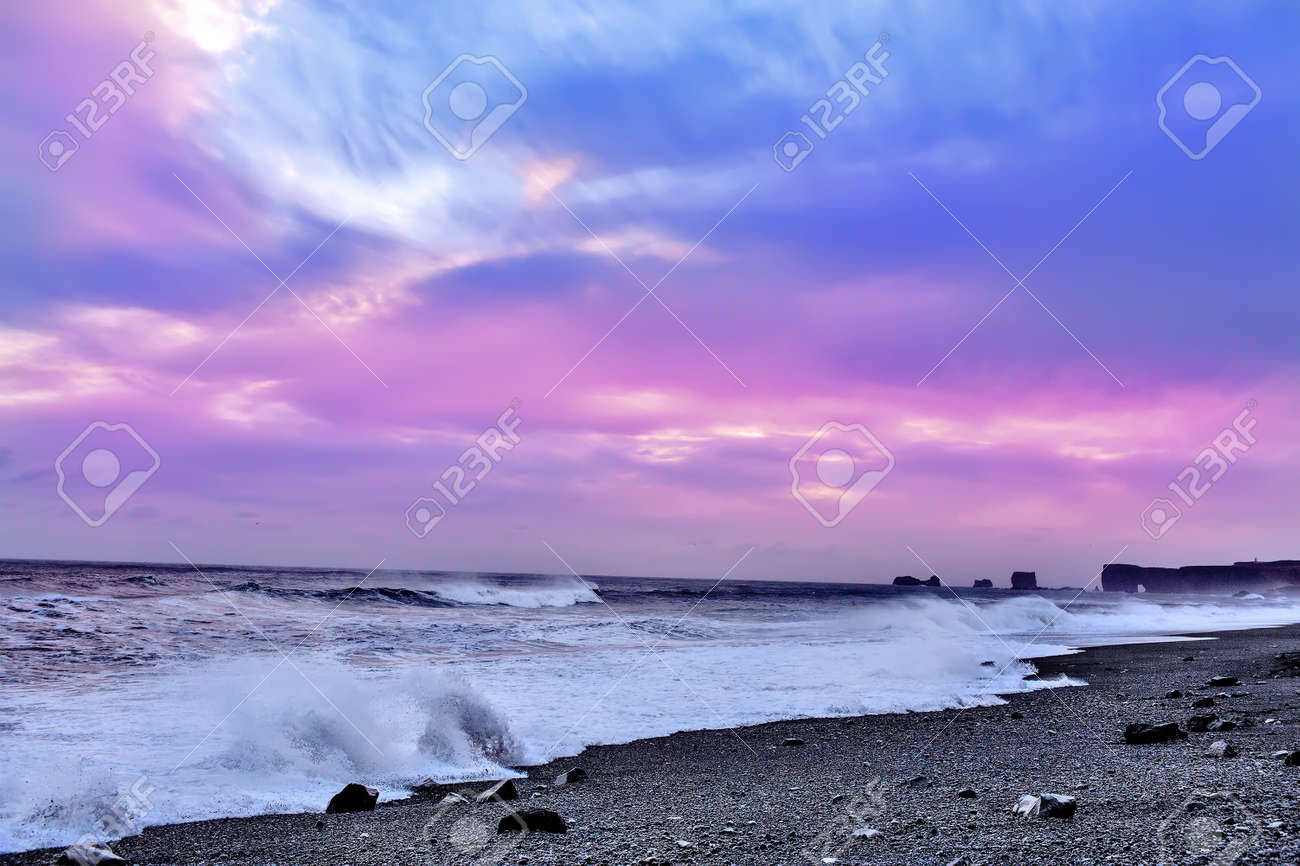 Surf On The Black Beach With Sand At Pink Sunset Background South Of Iceland