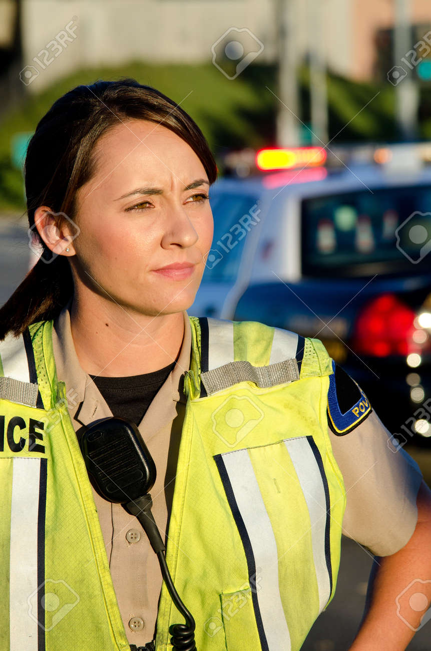 A female police officer staring and looking serious during a traffic control shift Stock Photo - 15401314