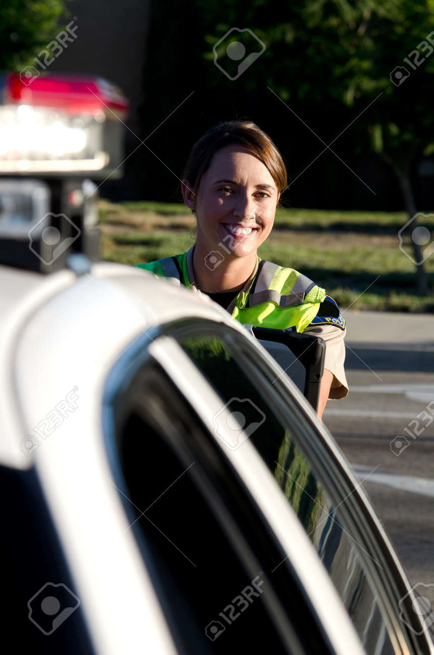 a female police officer smiles while typing on her lap top computer. Stock Photo - 15441984