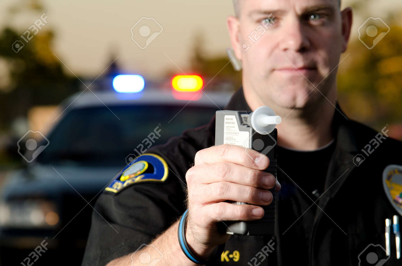 A police officer holds the breath test machine for a suspect to blow into with a police car in the background Stock Photo - 19225836