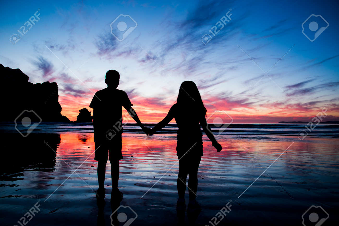 A brother and sister holding hands at sunset in Morro Bay, CA Stock Photo - 23047179