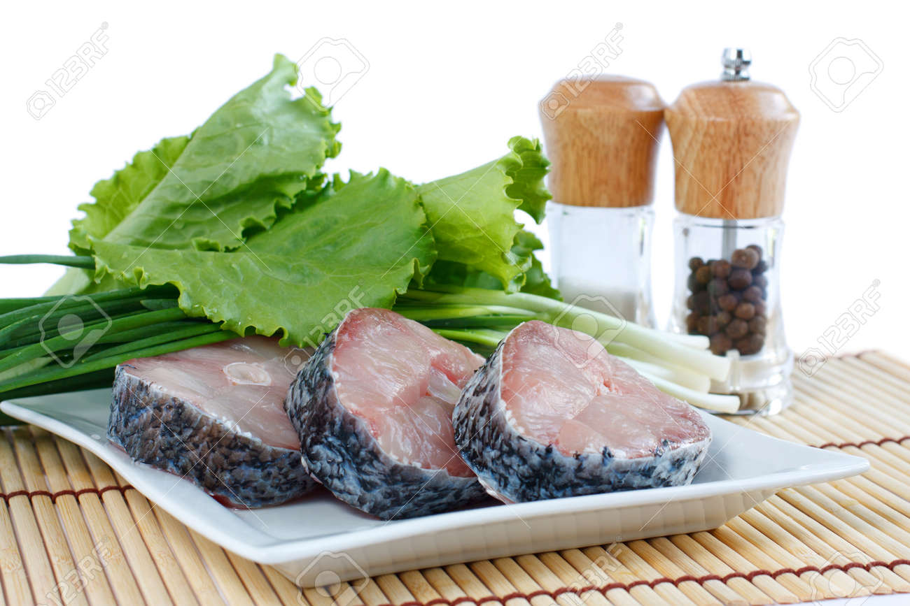 Fillet of fresh raw fish carp on a plate with herbs lettuce, green onions and spices  Isolated on white Stock Photo - 13705385