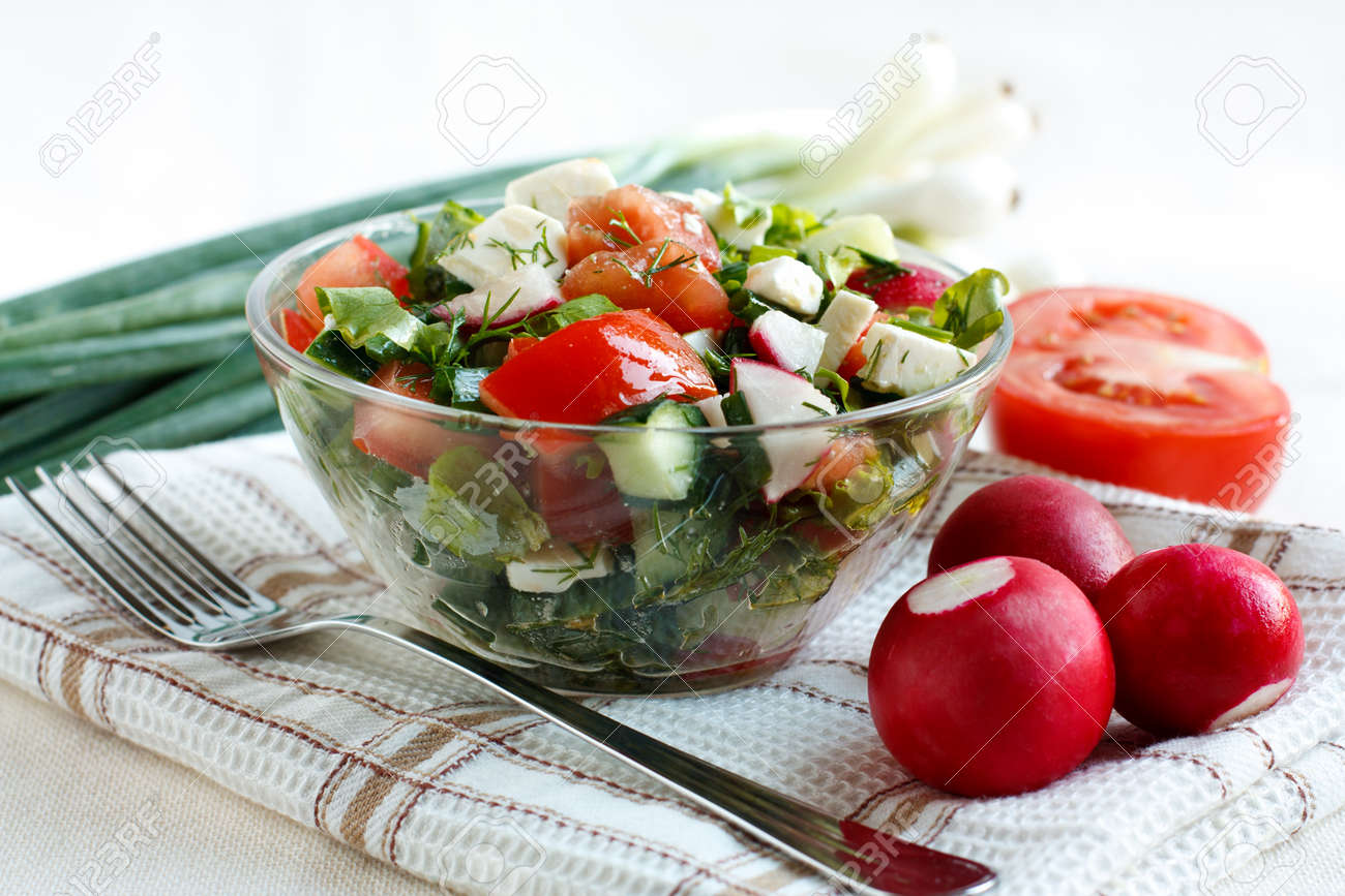 Salad with fresh vegetables and feta cheese in a salad bowl on a fabric napkin  Ingredients for the salad in the background Stock Photo - 13818170