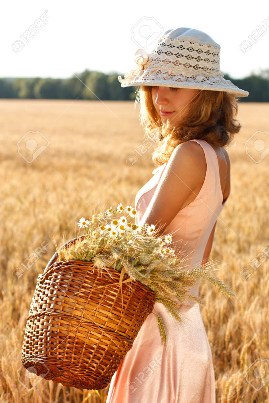 Beautiful woman with basket full of ripe ears of wheat and daisies in the wheat field on a sunny day Stock Photo - 14346765