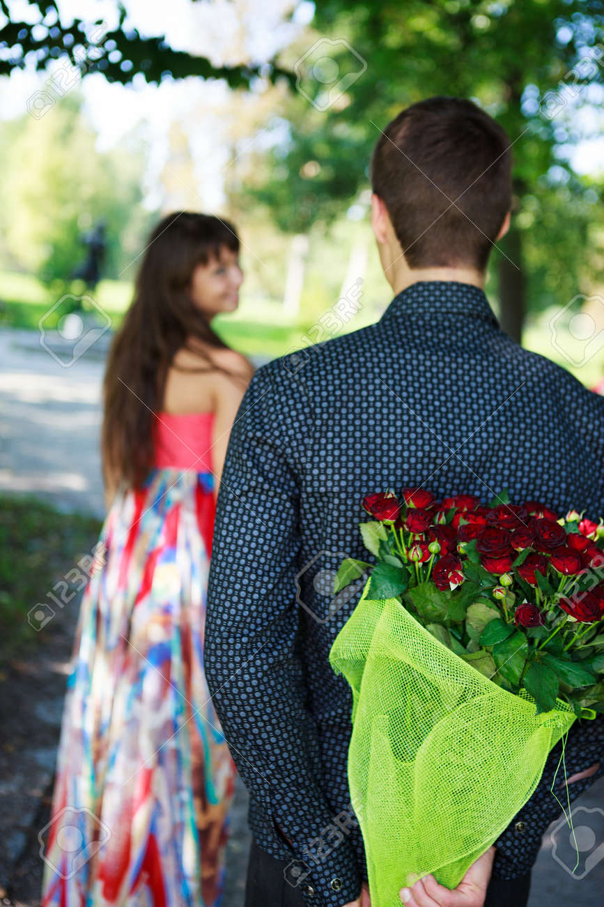 Young man keeps behind his back a bouquet of red roses gift a his girlfriend in a summer park Stock Photo - 17501163
