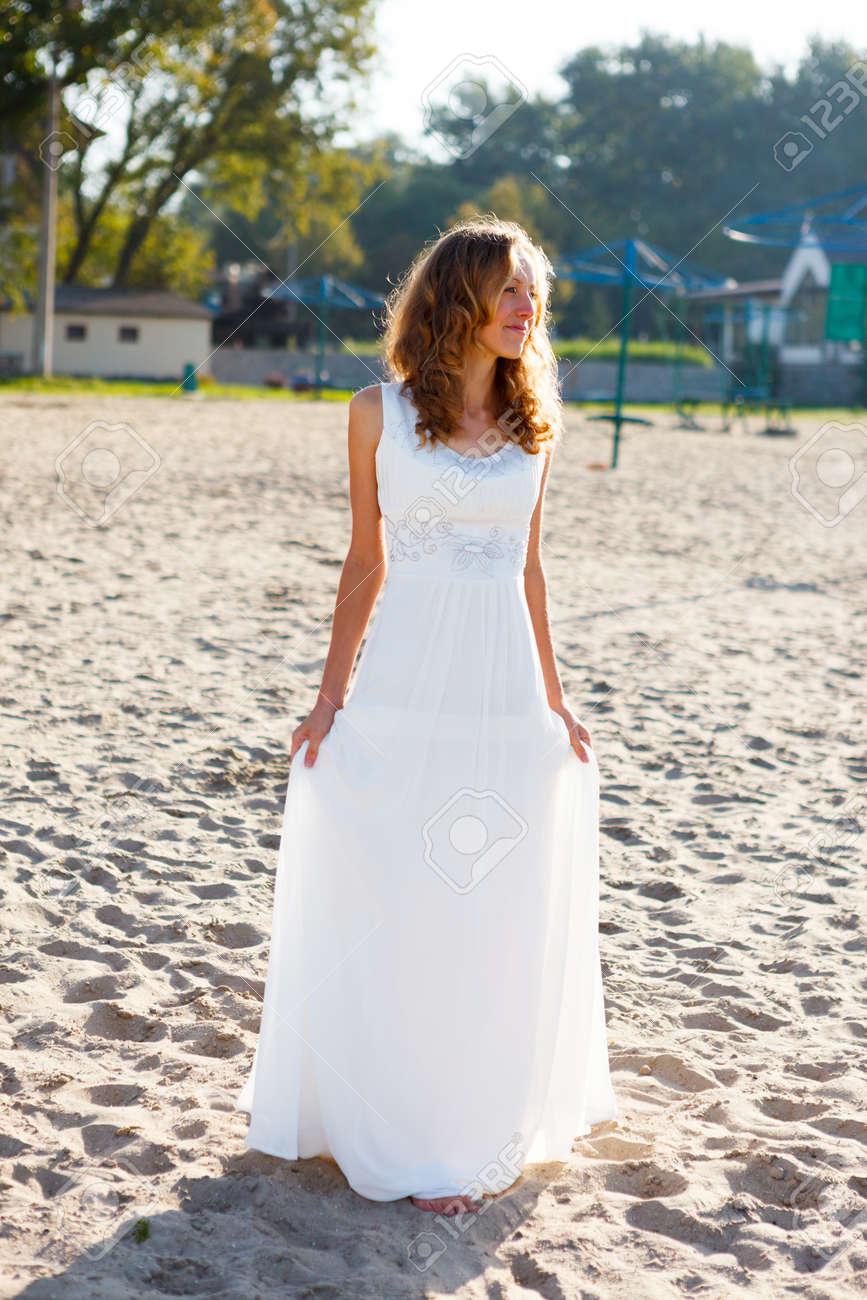 dc375e765 Foto de archivo - Joven mujer sonriente novia con un vestido blanco en la  playa en una mañana de sol al aire libre