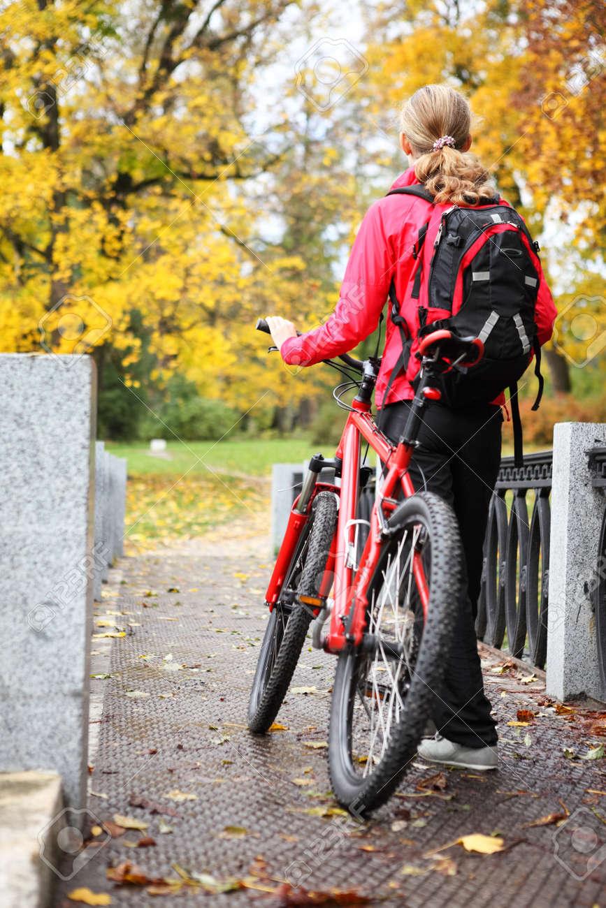 Mujer ciclista con la bici y caminar mochila bicicleta en parque del otoño