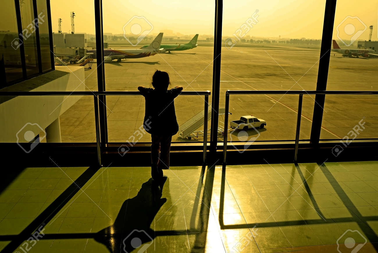 Silhouette of little girl at airport window Stock Photo - 24408400
