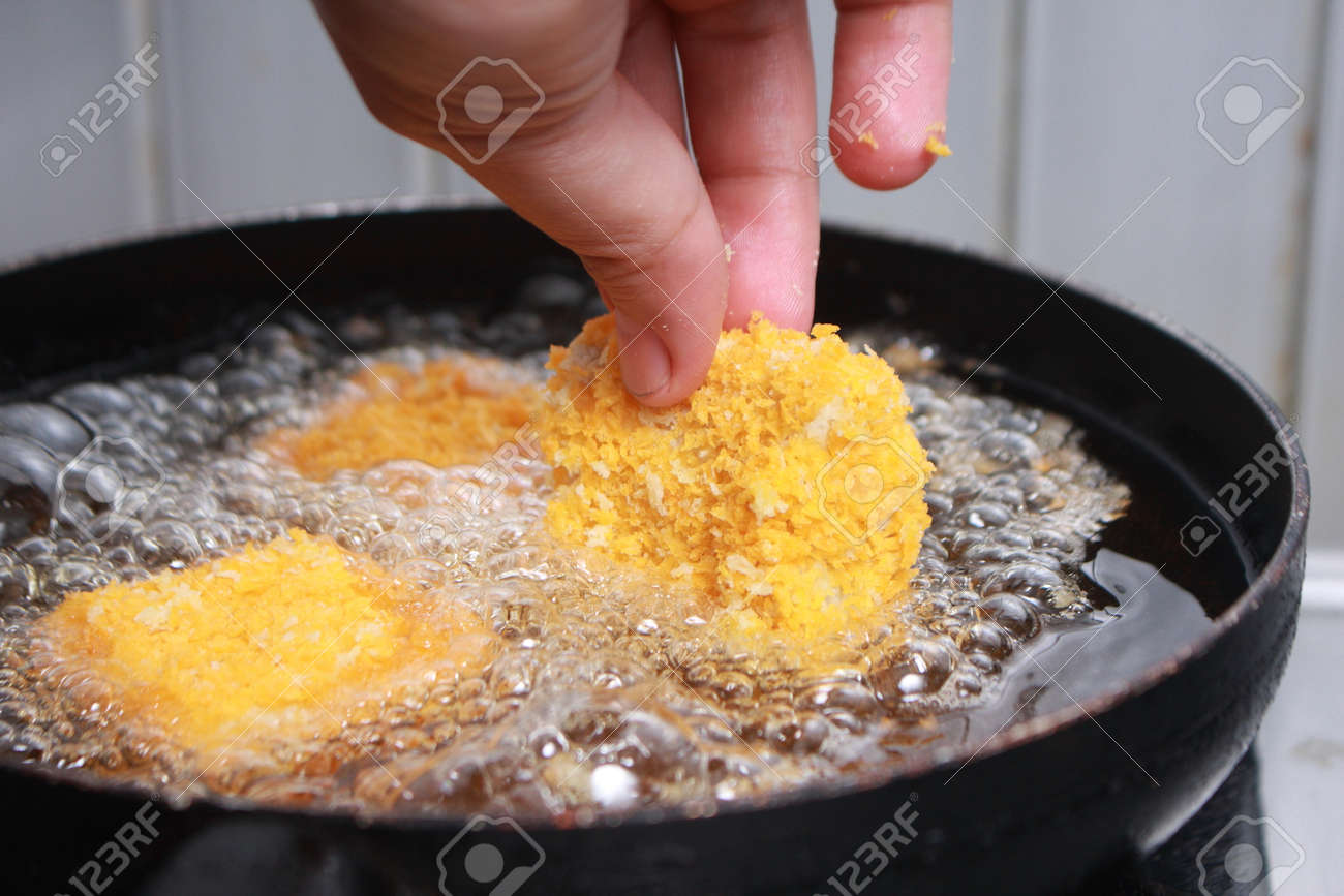 Close Up Image Of Chef Hand Putting Chicken Nuggets Tempura In To Hot Oil  Pan For