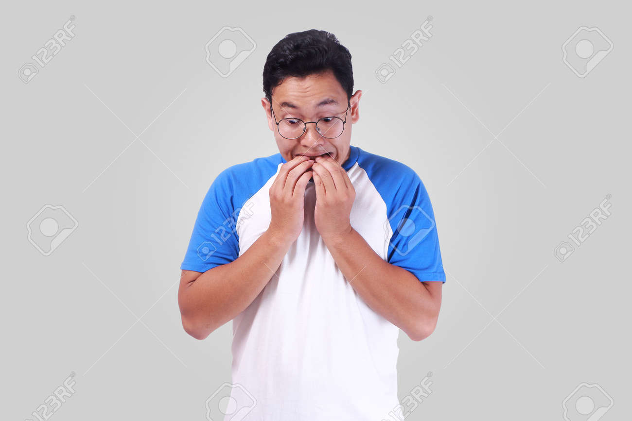 Portrait Of Young Funny Asian Man Biting His Nails As If He Is ...