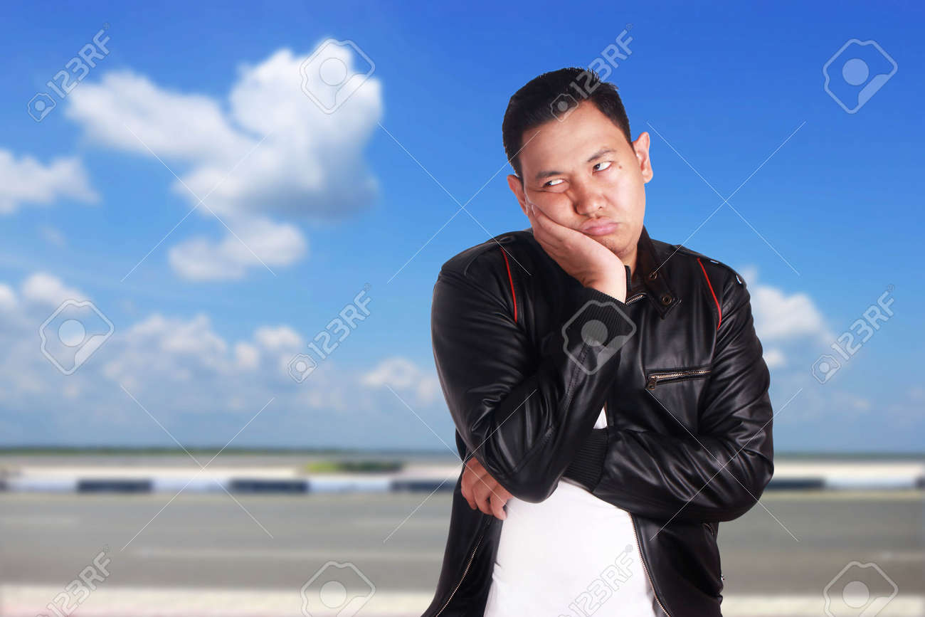 Portrait Of Young Asian Man Wearing Black Leather Jacket Shows