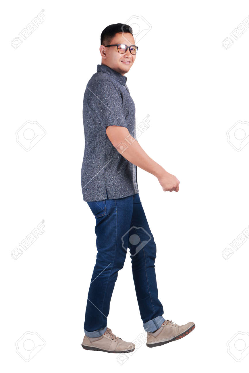 160dfe97bf Full body portrait of young Asian man wearing batik shirt and glasses  walking side view and