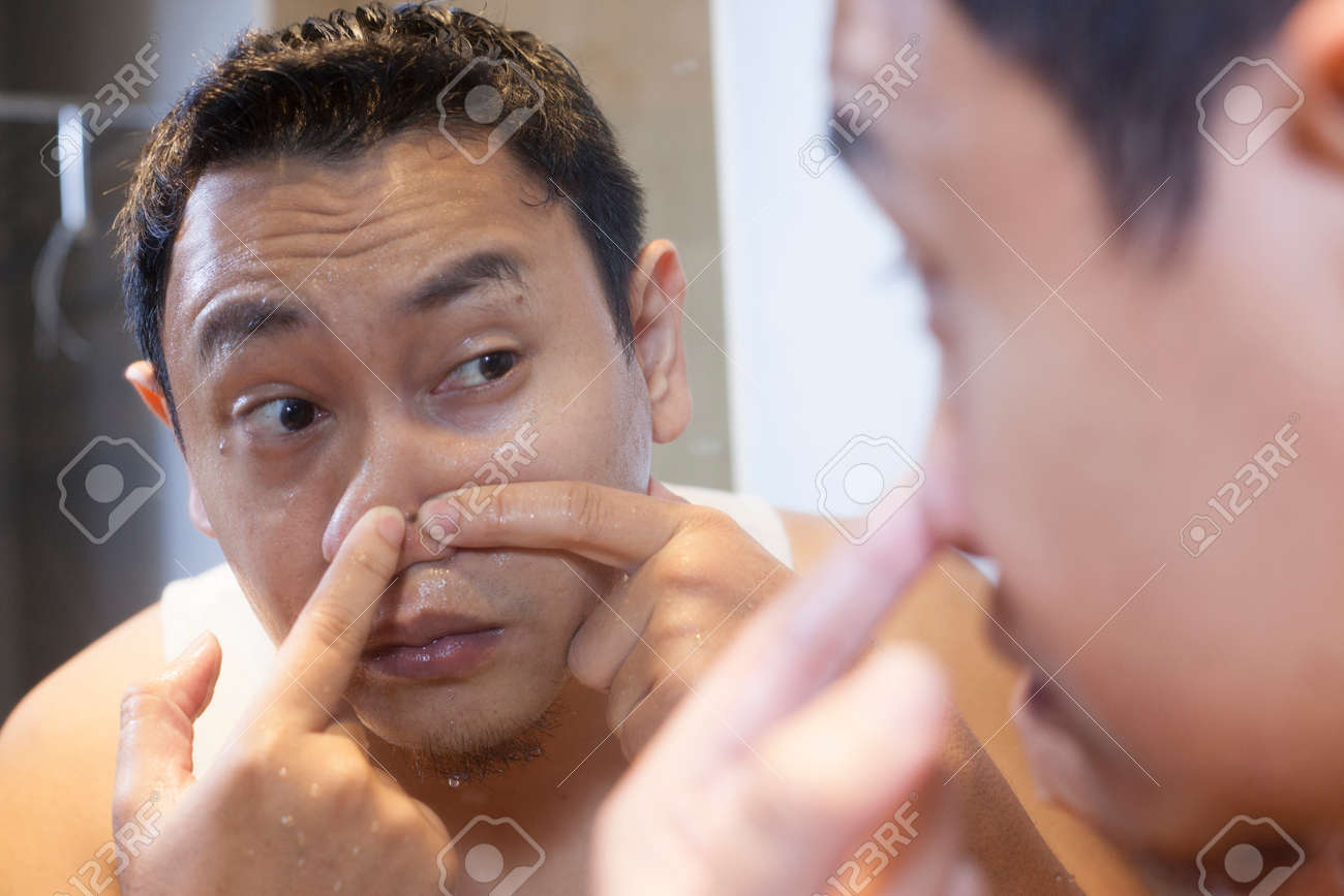 Portrait of attractive young Asian man squeezing acne on his nose, mirror reflection in bathroom - 123594681