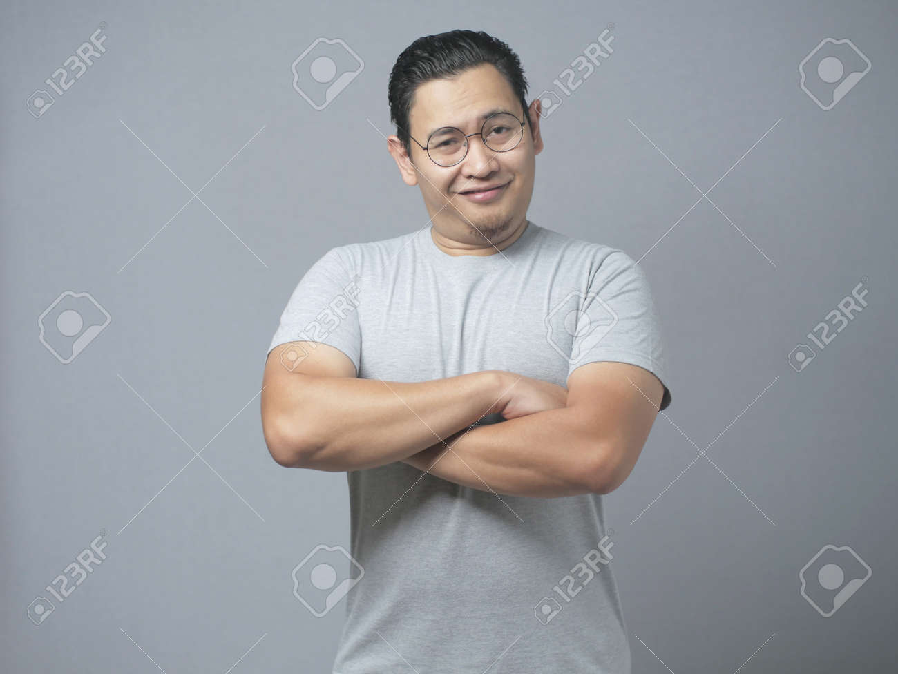 Photo image portrait of funny young attractive cute Asian man smiling happily, with arms crossed - 133176937