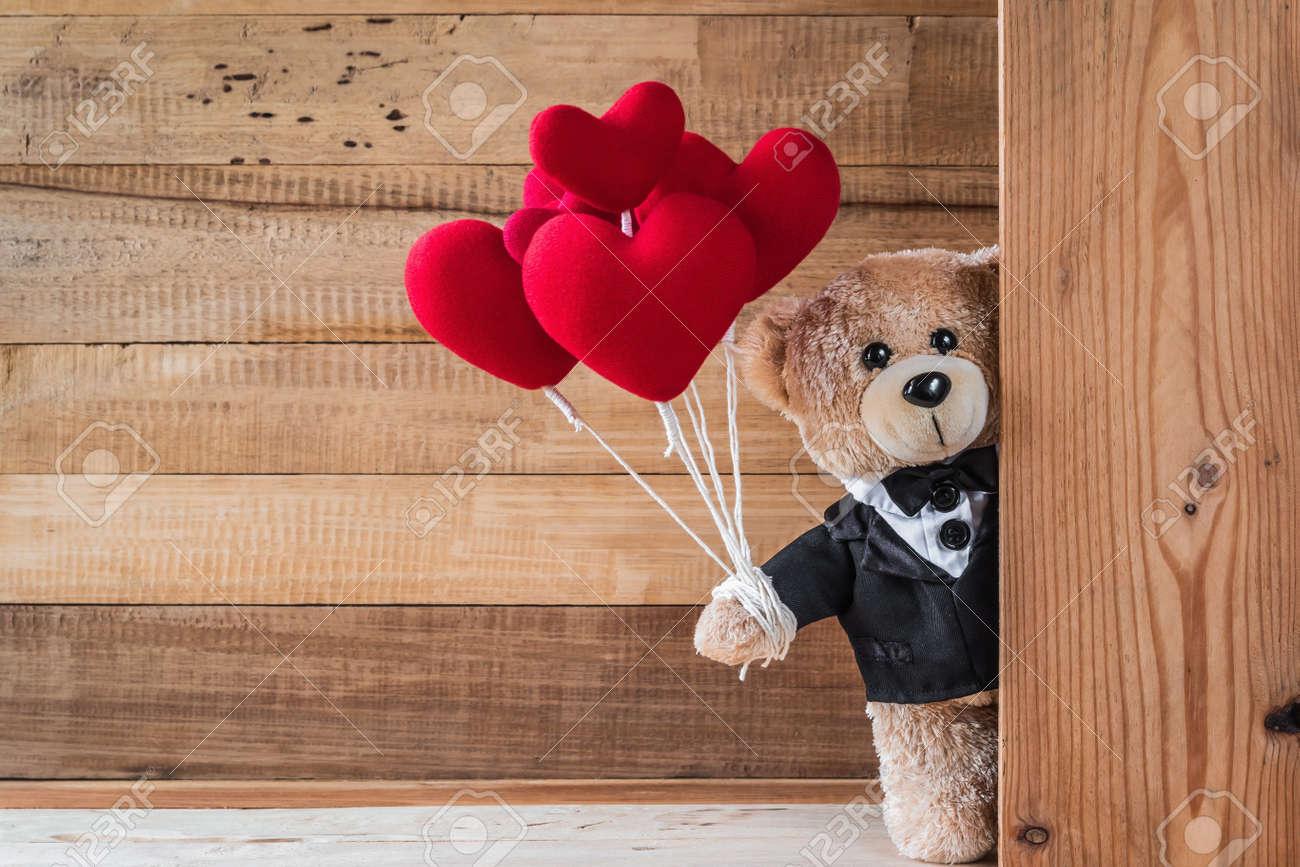 f455dd7b A photo of cute teddy bear holding heart-shaped balloon with..
