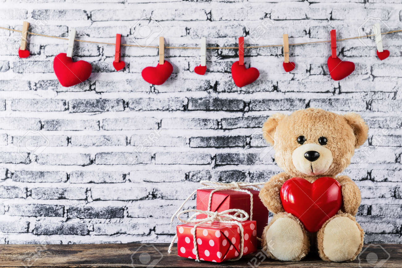 dd25ac02 A photo of Teddy bear holding a heart-shaped balloon with red..