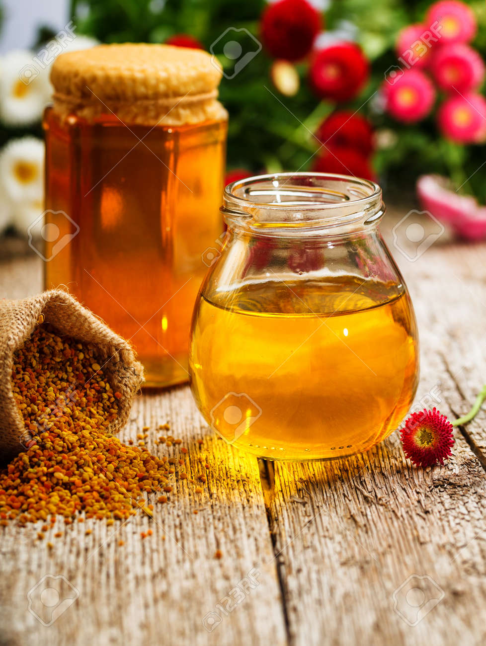 Still life of jars of honey, pollen and flowers Stock Photo - 21005262
