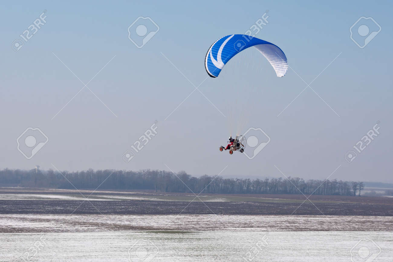 paramotor seen from the sky in France flying over snowy fields in winter with horizon and blue sky - 163394042