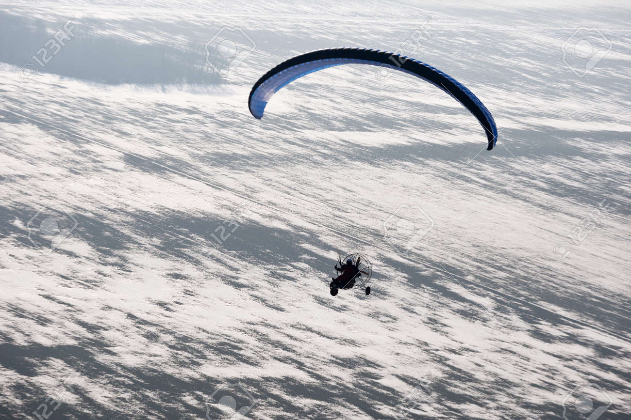 Aerial view paramotor buggy or motorized paraglider seen from the sky in France and flying over snowy fields in winter - 163394048