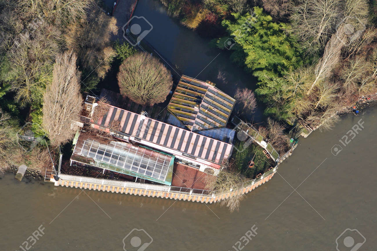 Mantes-la-Jolie, France - January 03, 2010: Aerial view of a house on the banks of the Seine river, in Yvelines department (78200), Ile-de-France region - 164841116