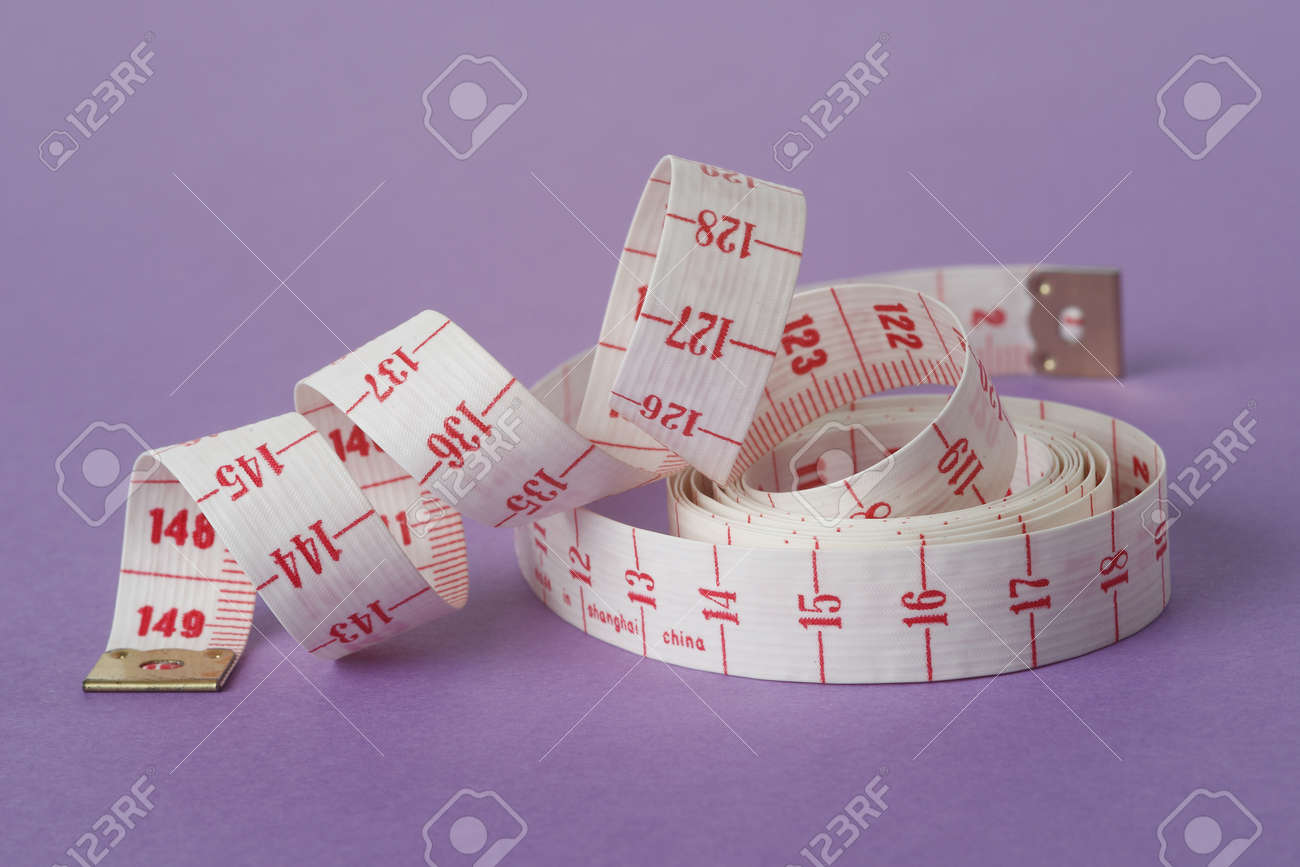Measuring tape isolated on purple background and partially unwound into a spiral - 164747948