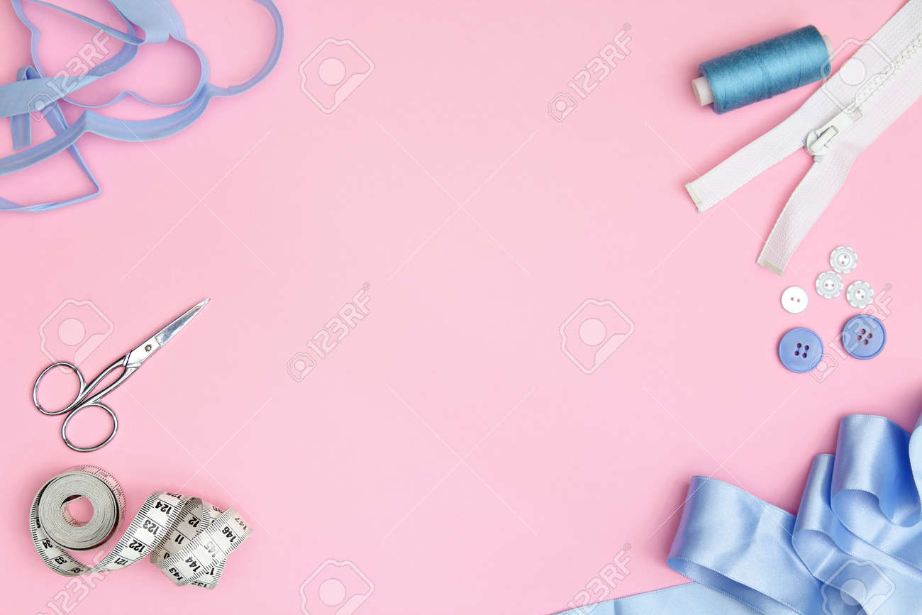 Sewing accessories on a pink background with needles, spool of thread, scissors and a tape measure - 165236948