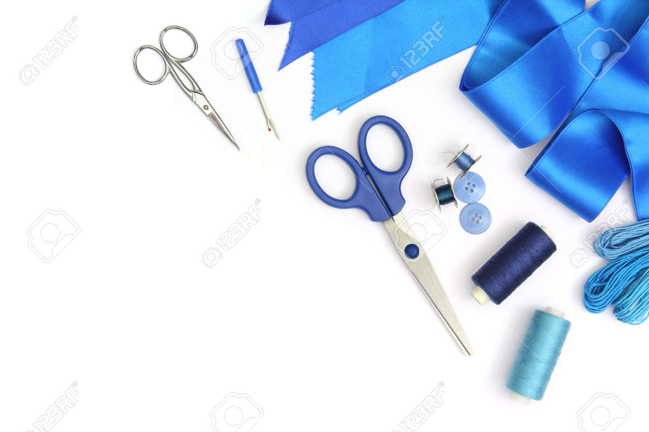 creative composition with blue sewing tools and accessories cut out and isolated in white frame with scissors, spools of threads and blue fabric ribbons - 165241508