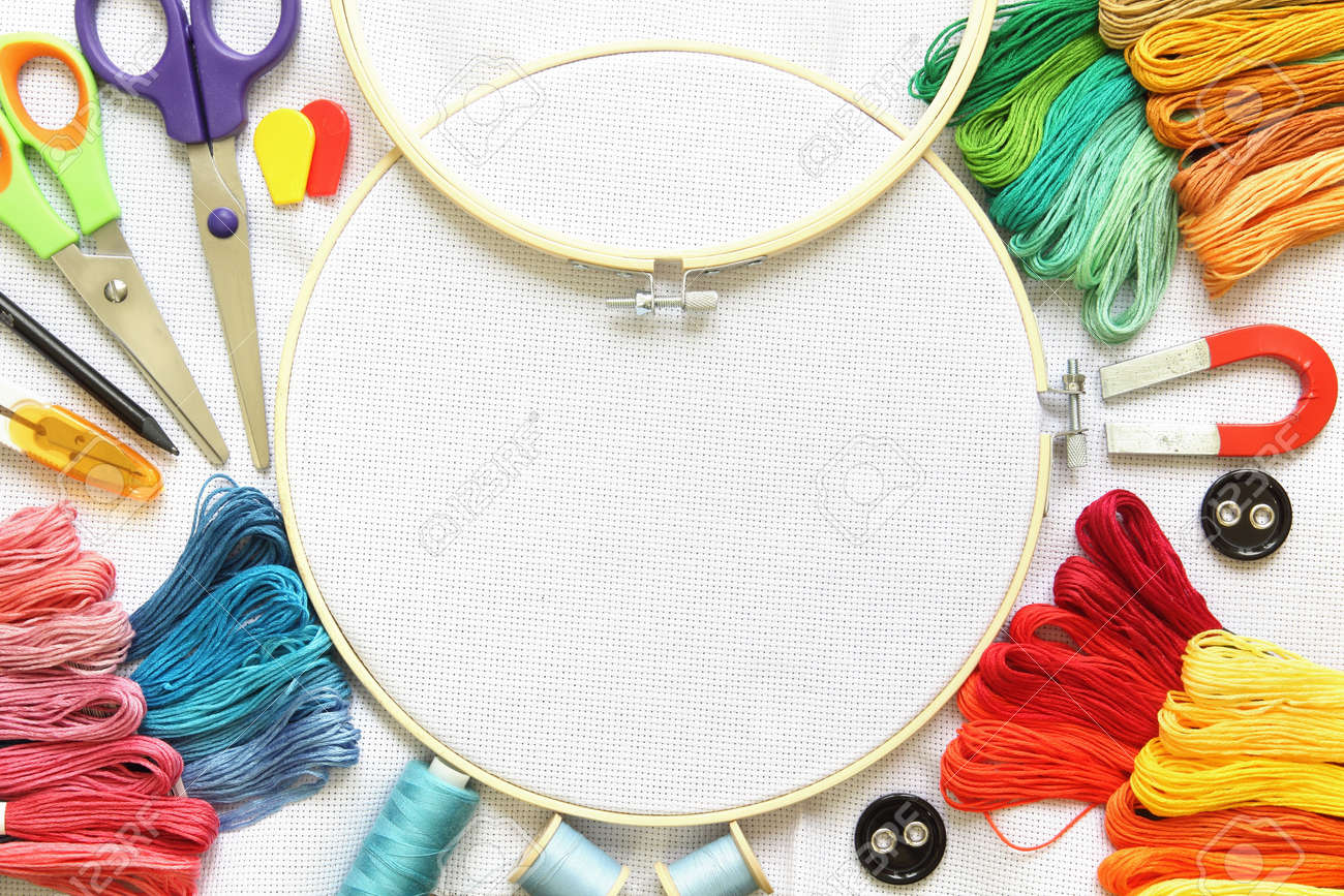 Multicolored embroidery accessories on white linen canvas. Embroidery hoop, spools of thread, needle and scissors. - 165250174