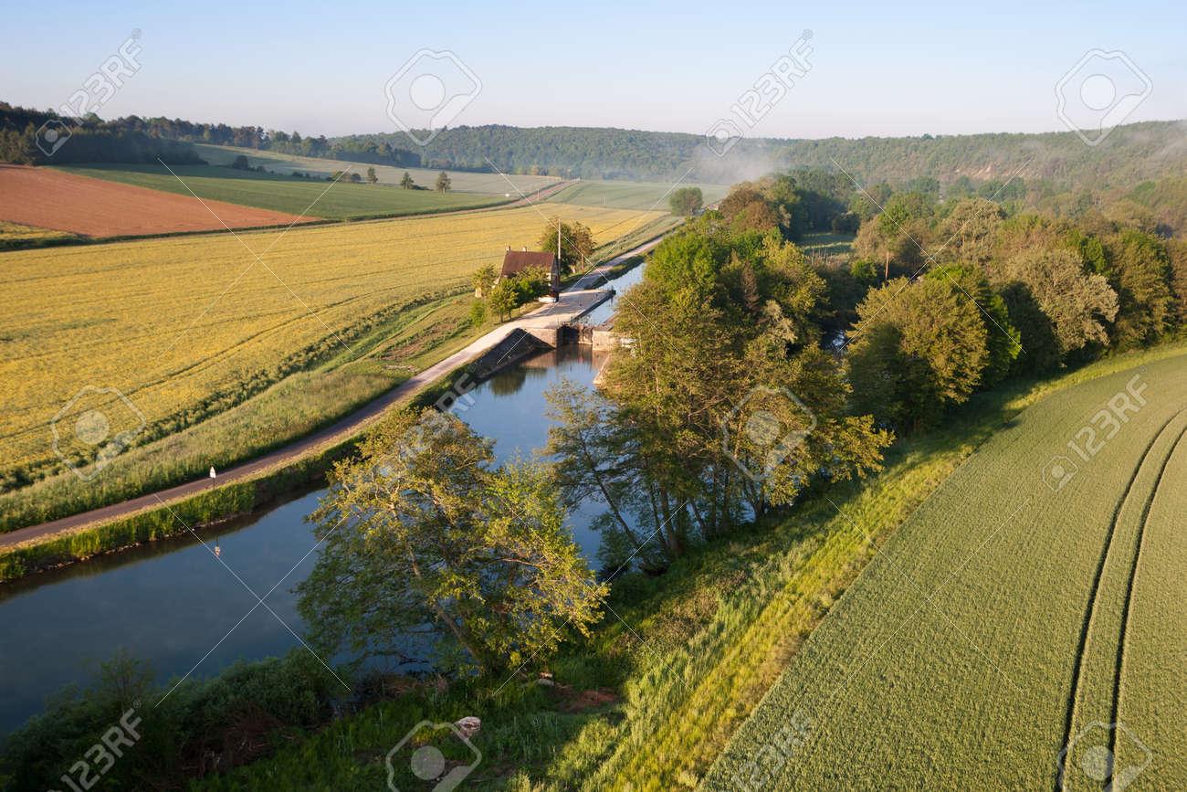 Lock of Ravereau seen from the sky in Merry-sur-Yonne, Nivernais canal, in Yonne department, Bourgogne-Franche-Comté region, France. - 165758113