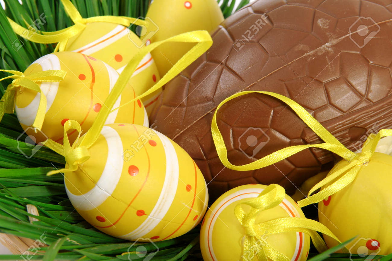 Yellow Easter eggs with ribbons on green grass, lying in a basket with a large chocolate egg - 165942273