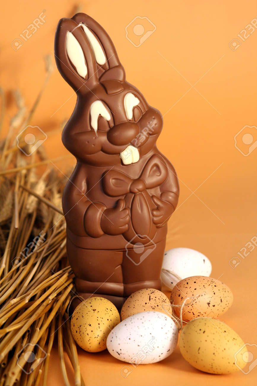 Big chocolate Easter bunny with eggs and ears of wheat on orange background - 165942408