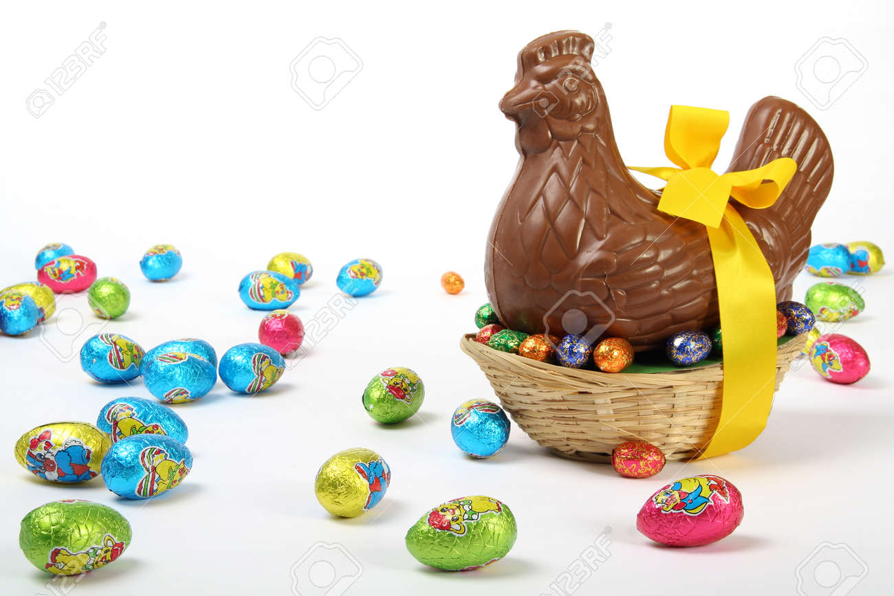 Chocolate Easter hen with yellow ribbon and bow, presented with colorful decorative eggs, isolated on white background - 165942599