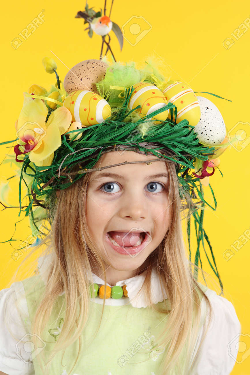 Portrait 7 year old girl dressed with a bird's nest hairstyle, made of spring flowers, Easter eggs and feathers. The child is looking at the camera. Easter concept on yellow background - 166403998