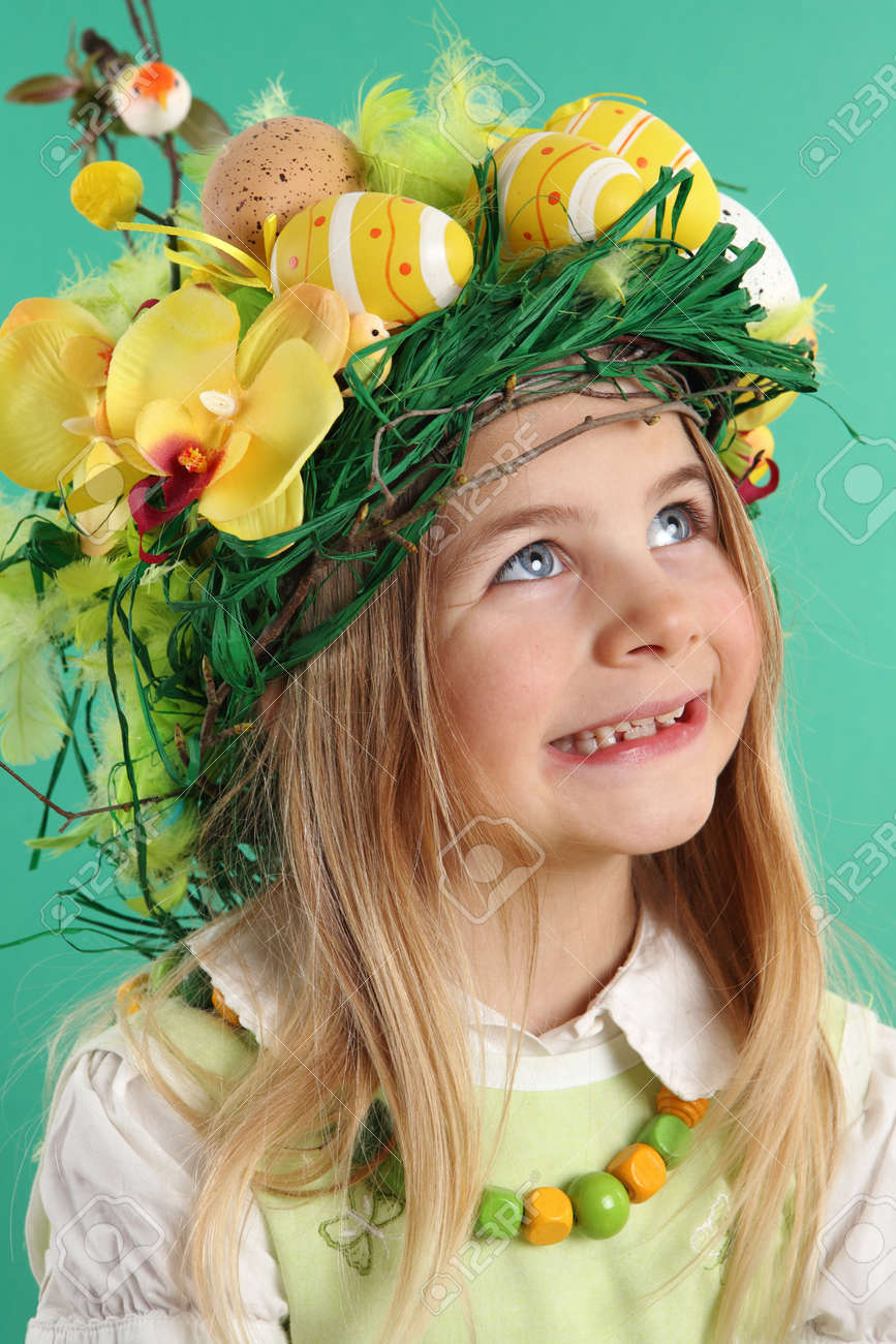 Happy Easter day. seven year old girl with festive Easter hairstyle made of yellow easter eggs, spring flowers and bird feathers. Smiling child looks up - 166403995