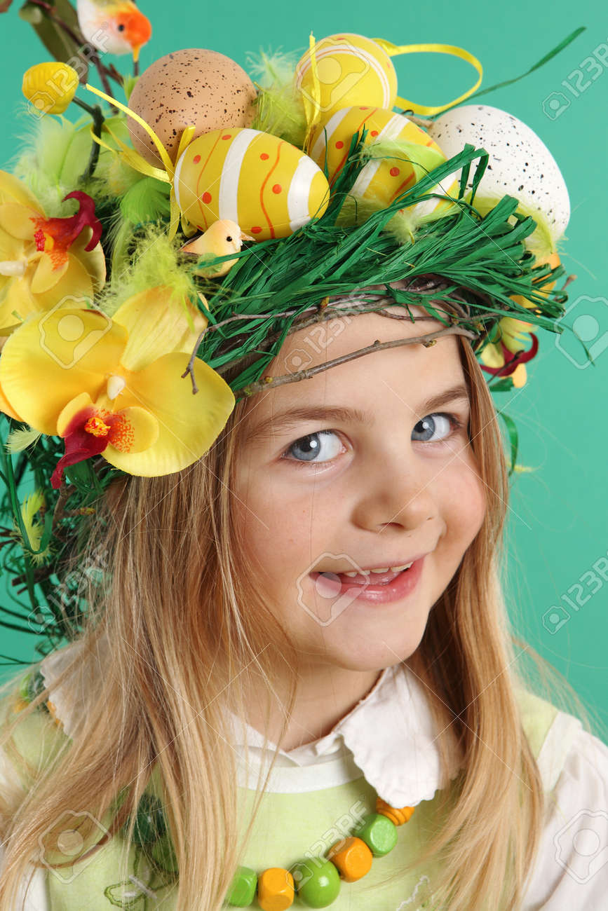 Portrait of a smiling blonde girl wearing hair dressing of yellow Easter eggs, spring flowers and bird feathers on a green background. The child looks at the camera - 166404000