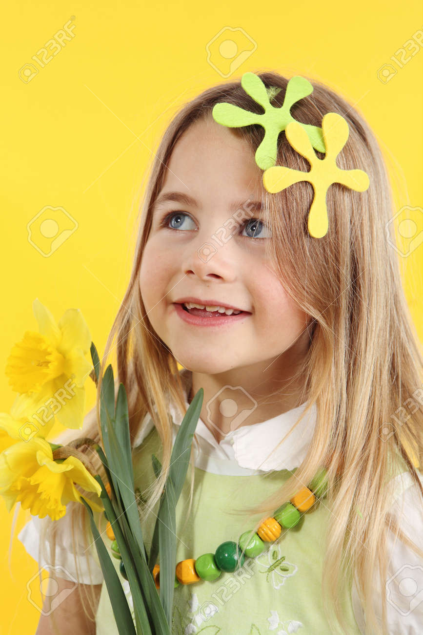 spring season concept: cute little girl with daffodil flowers for spring festival on yellow background. The child looks up to the side - 166404002