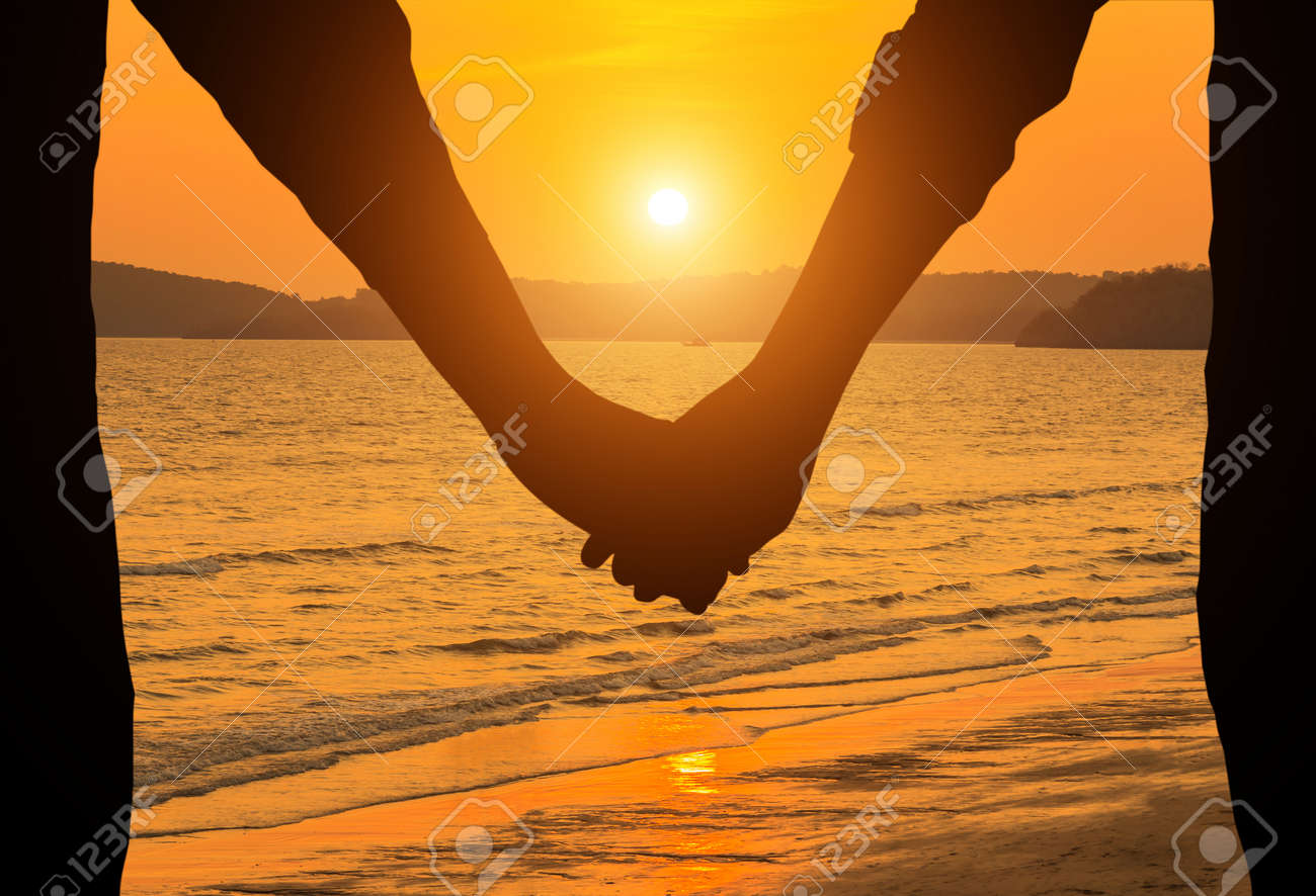 Silhouette Couple Holding Hands In Sunset Background Stock Photo ... for Couple Holding Hands Silhouette Sunset  150ifm