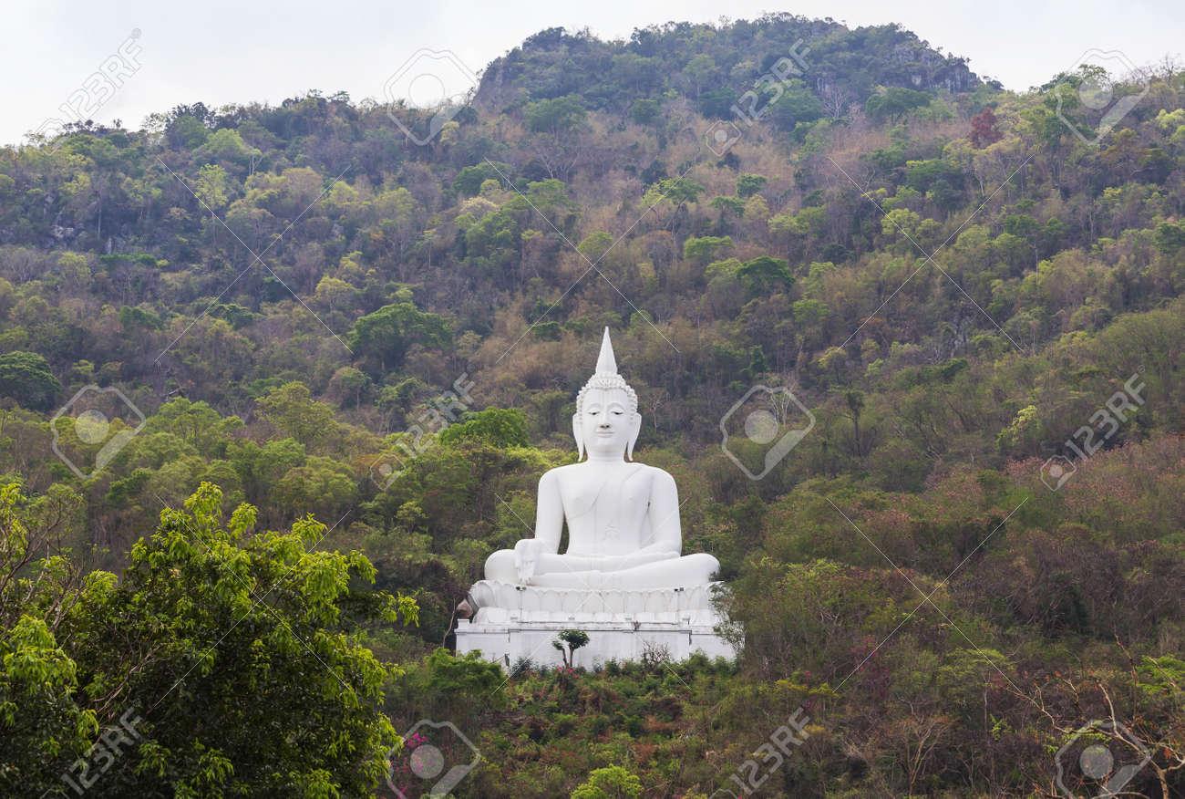 big white buddha statue sitting on the mountain at pakchong stock