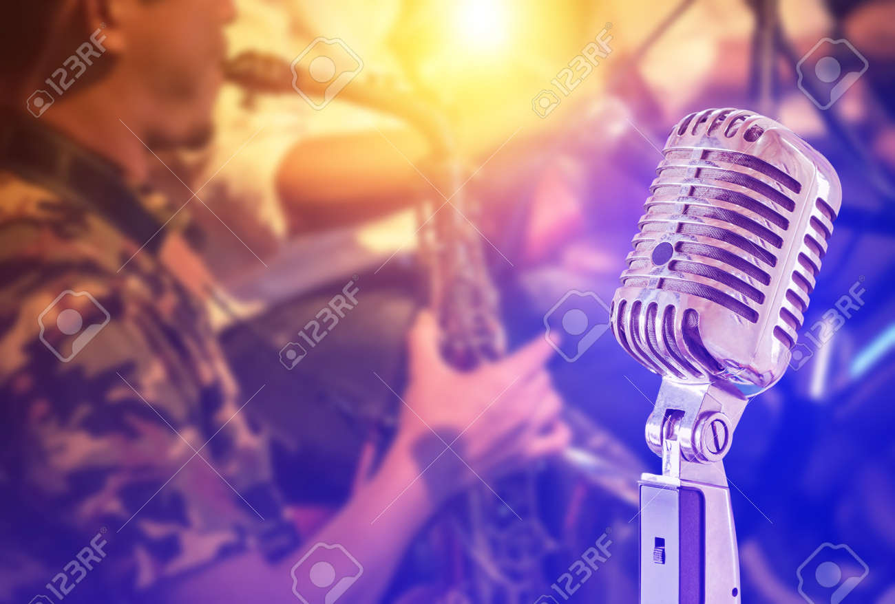 Close up retro microphone with musician playing saxophone on