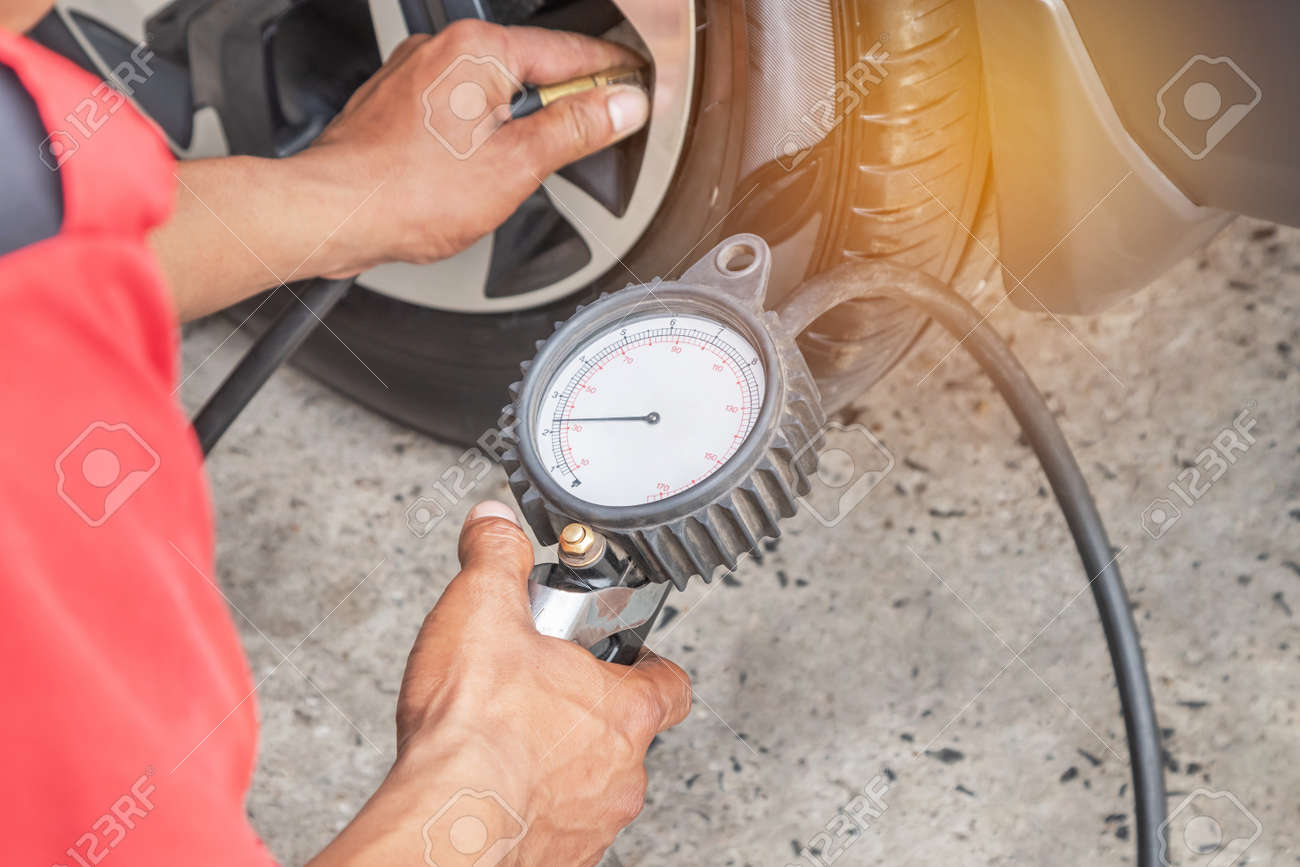 Close up mechanic inflating put air into the tyre and checking air pressure with gauge pressure in service station - 111684579