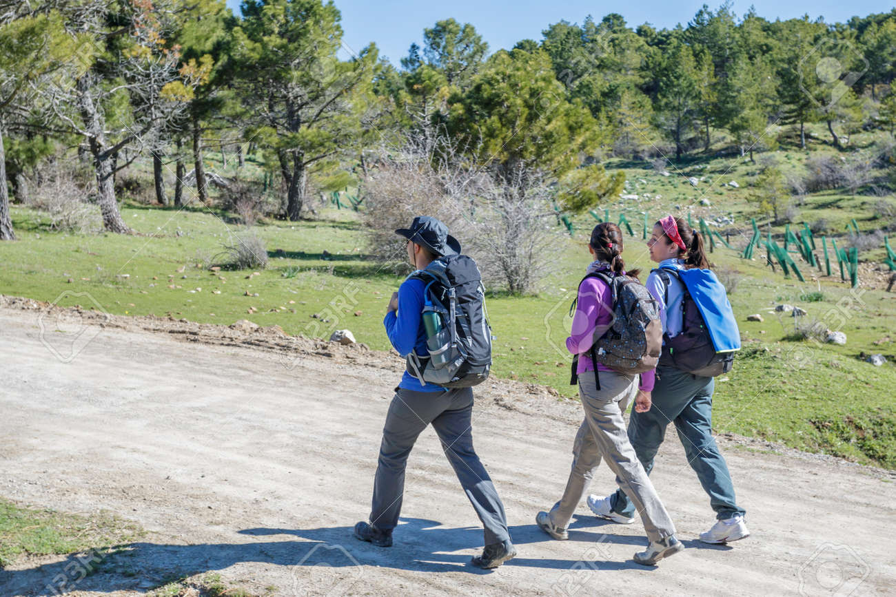 e444184aad Three People Hiking At The Mountain In A Sunny Day Stock Photo ...