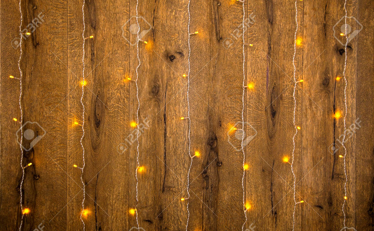 Yellow fairy lights on a wooden wall holyday background stock stock photo yellow fairy lights on a wooden wall holyday background aloadofball Choice Image