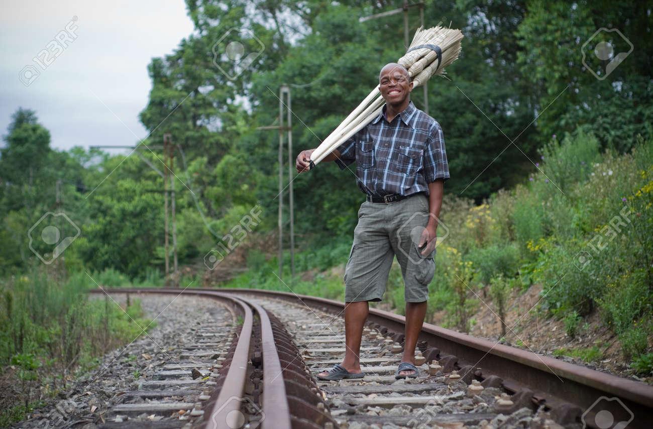 Stock photograph of a black South African entrepreneur small business broom salesman on railway line in Hilton, Pietermaritzburg, Kwazulu-Natal Stock Photo - 17536866