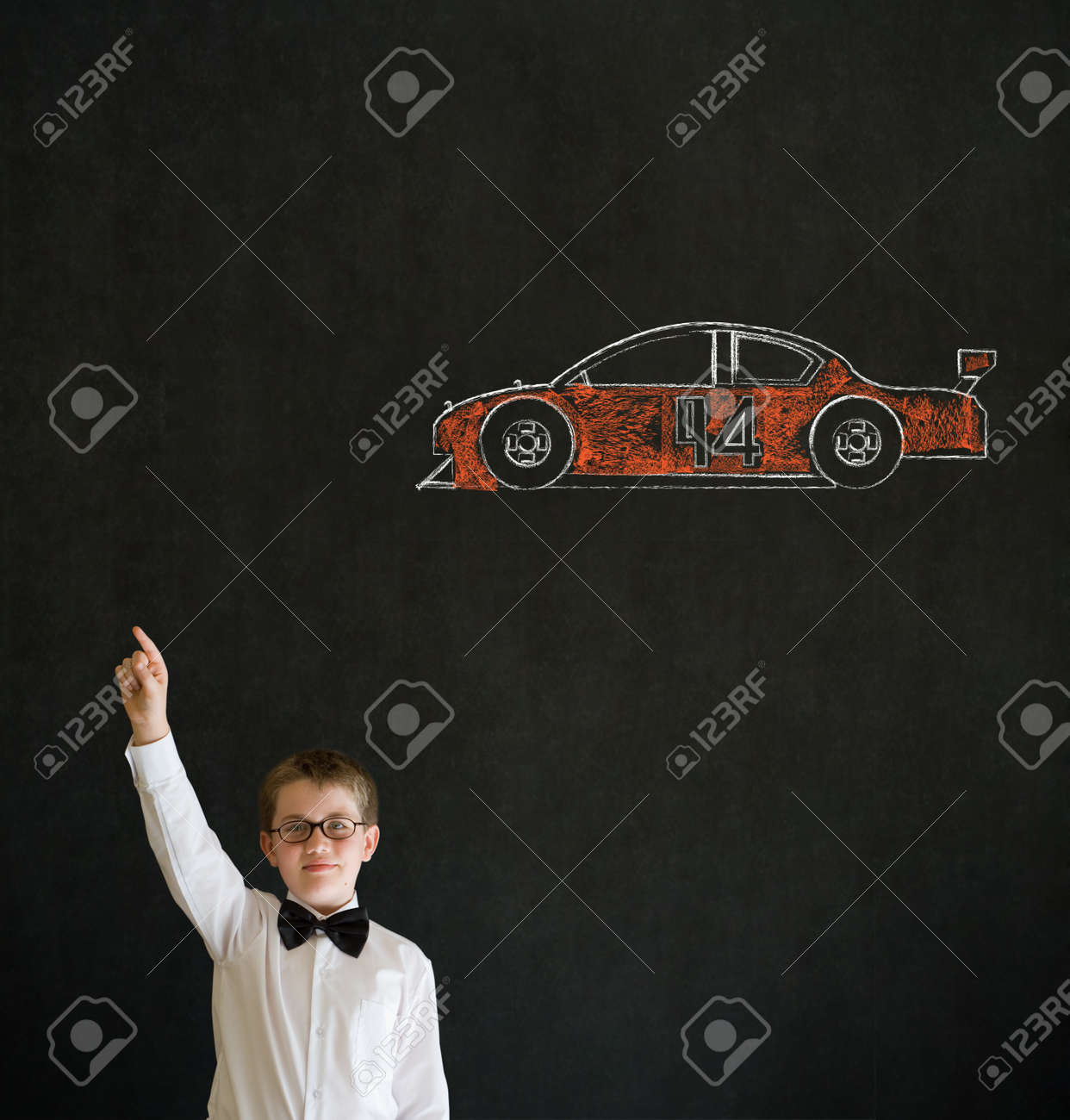 Hand up answer boy dressed up as business man with Nascar racing fan car on blackboard background Stock Photo - 19727495