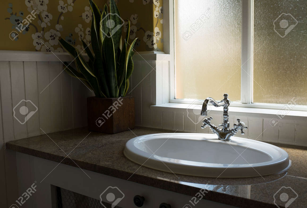 . Old retro water tap basin in modern bathroom toilet with window